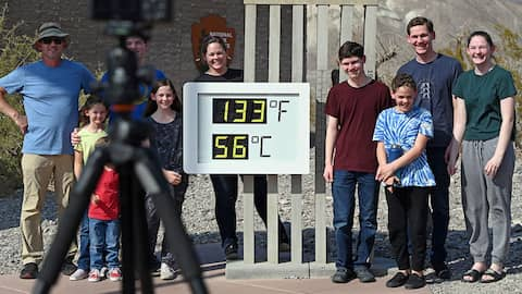 People visit the unofficial thermometer reading 133 degrees Fahrenheit/56 degrees Celsius at Furnace Creek Visitor Center on July 11, 2021 in Death Valley National Park, California. An excessive heat warning was issued for much of the Southwest United Sta
